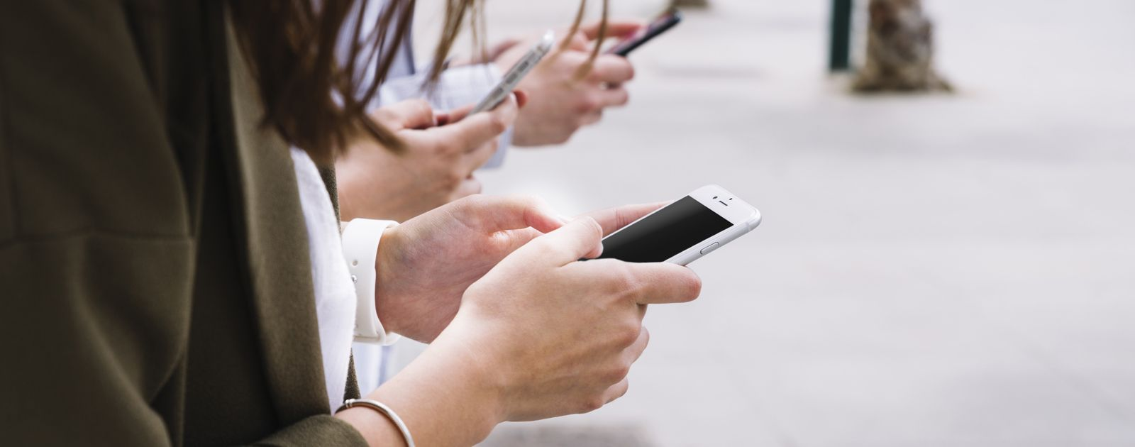 three-people-using-cell-phone-outdoors_movil_cabecera